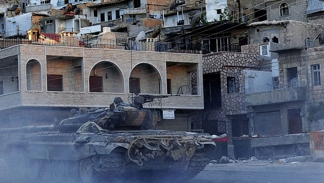 A Syrian government tank is seen during clashes with Free Syrian Army fighters, not pictured, in Maaloula village, northeast of the capital Damascus, Syria.