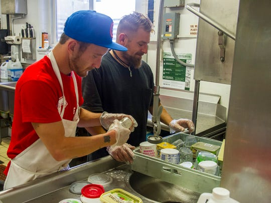 Travis Miller, left, and Nicholas Gamble clean dishes