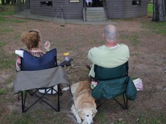 Kathy Klement, Rothschild, and Mike Sherfinski, Schofield, sit with Klement's dog, Gracie and listen during the Wausau Concert Band's performance at Marathon Park in Wausau, Thursday, June 27, 2013.