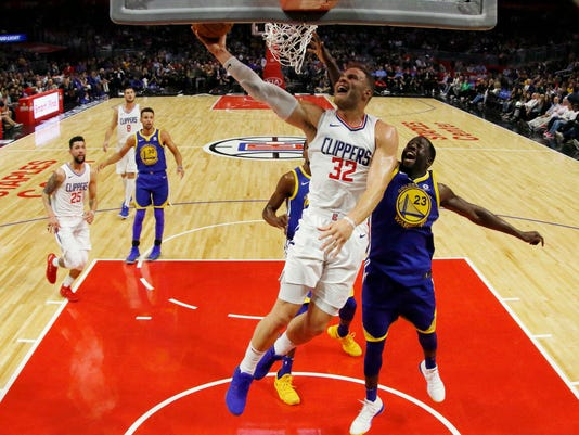 Los Angeles Clippers forward Blake Griffin, center, goes to the basket while being defended by Golden State Warriors forward Draymond Green, right, during the first half of an NBA basketball game, Monday, Oct. 30, 2017, in Los Angeles. (AP Photo/Ryan Kang)