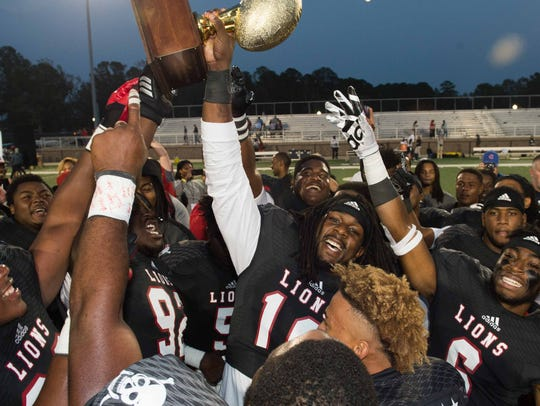 East Mississippi players hoist the trophy following