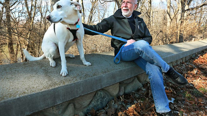 Photojournalist Bill Foley and his faithful dog, Sophie, at the very spot along White River where they were attacked by a neighbor's dog. Foley, who'd survived more than a decade of trouble in the Middle East, nearly died of a dog bite.