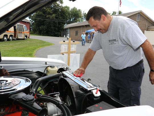 Pete Mercado, of the Town of Poughkeepsie, goes over his 1972 Chevrolet Nova SS that he and his son, Edward have been restoring during the First Responder Memorial Car Show at New Hackensack Fire Department in Wappingers Falls on Saturday.