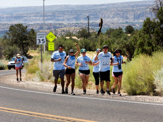 Members of the International Indigenous Youth Council make their way up College Boulevard Monday toward Bureau of Land Management field office in Farmington.