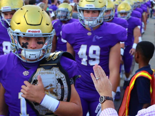 Fans greet members of the CBHS football team as they