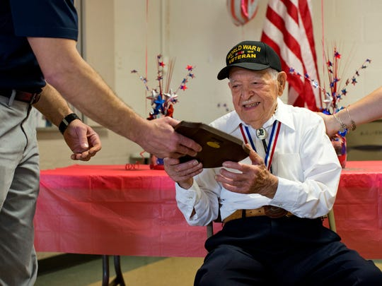 Walter Krupa, a World War II veteran, is presented a plaque by the St. Clair County Department of Veteran Affairs during his 100th birthday party Saturday, May 9, 2015 at American Legion Post 525 in Smith's Creek.