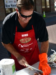 Jeff Davis with the Diamond B booth at the United Way Wild Cook-Off cuts up pork tenderloin.