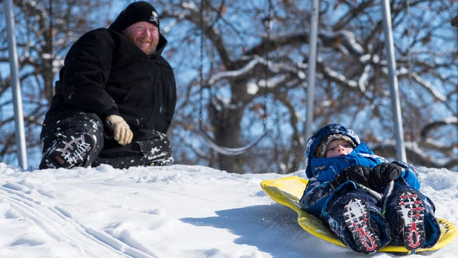 Michael Thomas, of Port Huron, left, watches his son Sawyer, 5, slide down the sledding hill at the Palmer Park Recreation Center Monday. Sawyer attends Garfield Elementary and was given the day off due to snow.