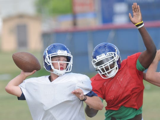 Cooper quarterback Henry Farrell, left, prepares to throw a pass while under pressure during the Cougars' spring practice Monday at the Cooper practice field.