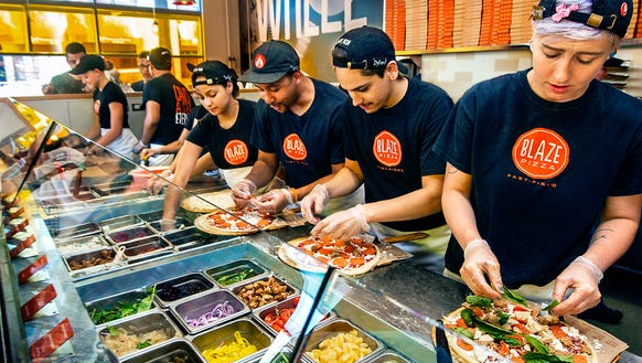 Assembly-line production at Blaze Pizza.