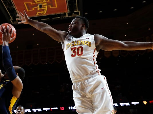 Iowa State guard Deonte Burton (30) tries to block a shot by West Virginia guard Jevon Carter, left, during the first half of an NCAA college basketball game, Tuesday, Jan. 31, 2017, in Ames, Iowa. (AP Photo/Charlie Neibergall)