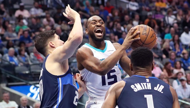 Mar 24, 2018; Dallas, TX, USA; Charlotte Hornets guard Kemba Walker (15) looks to pass as Dallas Mavericks guard Dennis Smith Jr. (1) and forward Doug McDermott (20) defend during the second half at American Airlines Center.