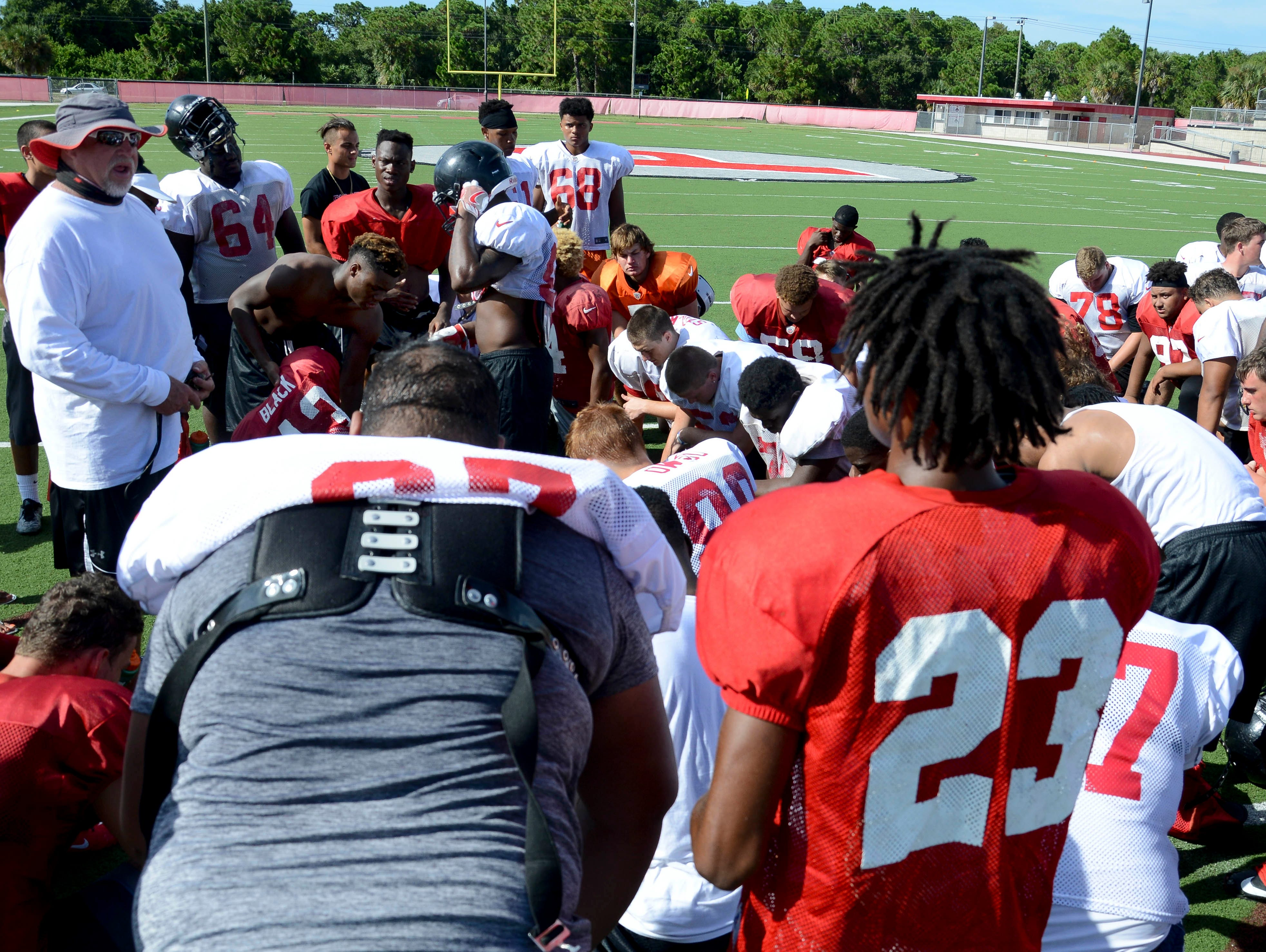 Palm Bay High football players listen to coach Dan Burke during practice Wednesday.