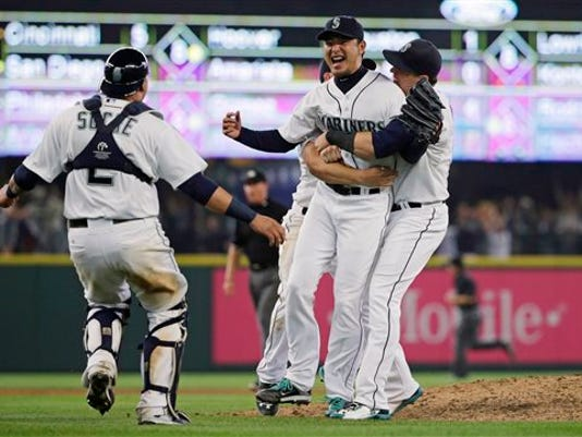 Seattle Mariners starting pitcher Hisashi Iwakuma, second from right, is greeted by teammates, including catcher Jesus Sucre, left, after Iwakuma threw a no-hitter in a baseball game against the Baltimore Orioles, Wednesday, Aug. 12, 2015, in Seattle. The Mariners won 3-0.