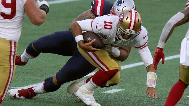 Patriots defensive lineman Lawrence Guy, rear, sacks 49ers quarterback Jimmy Garoppolo during the first half Sunday.