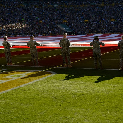 Soldiers take part in holding a large American flag
