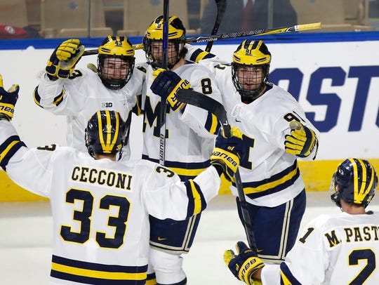 Michigan's Quinn Hughes (43) celebrates his goal with teammates during the first period against Boston University in the Northeast regional final in Worcester, Mass. on March 25.