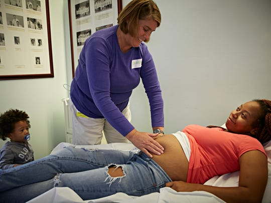 While her Nephew Roman waits patiently, mother-to-be Shamika Norman gets a prenatal checkup from Nurse midwife Elizabeth S. Sushereba, MSN, CNM.