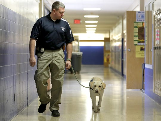 Menasha school liaison officer Jeff Jorgenson and K9 Geller walk the halls at Butte des Morts Elementary School, where the officer and the dog are a regular presence.