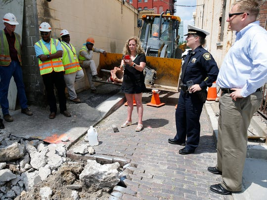 Margy Waller (center) stands with employees of the Greater Cincinnati Water Works, Cincinnati Police and Councilman Chris Seelbach (far right) in Adrian Alley in Over-the-Rhine as she refused to leave in order to protect historic bricks that were being removed on Monday.