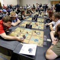 Gregory Kettler, left, makes a move while playing Golem Arcana during Gen Con at the Indiana Convention Center, on Saturday, August 16, 2014, in Indianapolis.