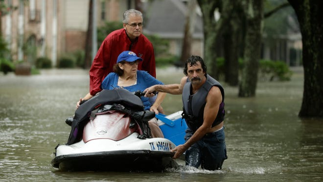 People evacuate a Houston neighborhood inundated on  Aug. 28, 2017.