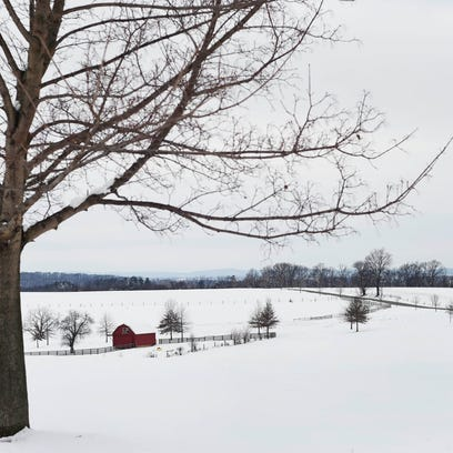 A farmhouse surrounded by snowy field on Overlook Street