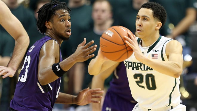 Michigan State guard Travis Trice looks to pass the ball against Northwestern guard JerShon Cobb at Jack Breslin Student Events Center.