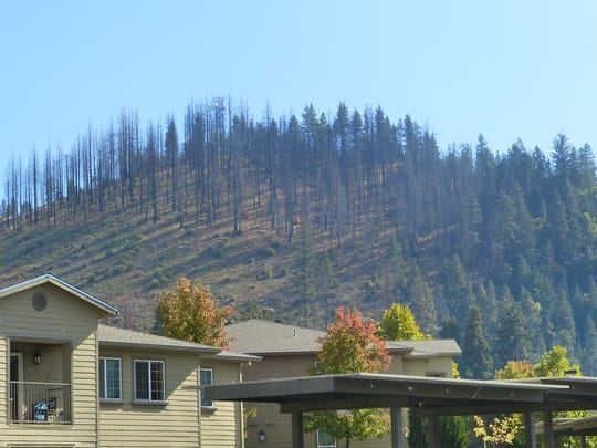 A fire-scarred hill behind some apartments in Weed, Calif. acts as a permanent reminder of the 2014 Boles Fire, which destroyed about a third of the city's homes.