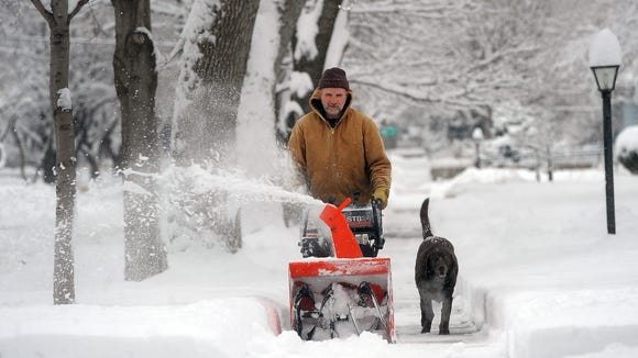 Tom O'Hara snow blows the sidewalk along First Avenue
