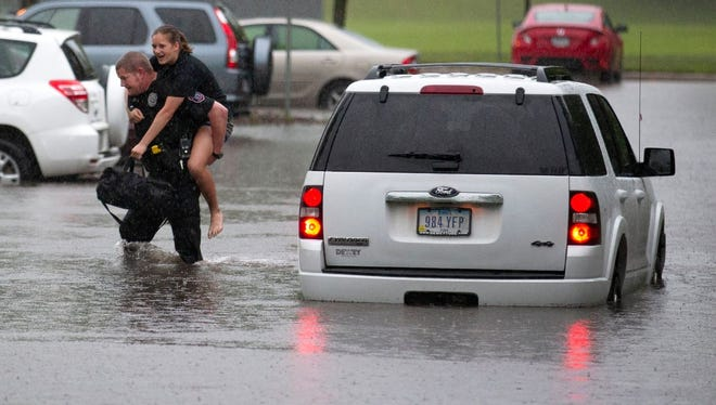 ISU Police Officer Doug Hicks rescues a woman from a flood-stalled vehicle at the Lied Recreation Athletic Center.