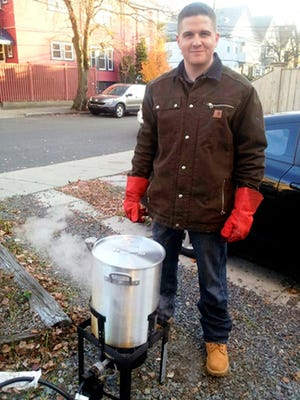 In this November 2012 file photo provided by Nicole Lynch, her brother, Sean Collier, stands in his driveway in Someville, Mass., frying a turkey for his annual kickball Thanksgiving gathering. Investigators said Collier, a Massachusetts Institute of Technology police officer, was shot to death Thursday, April 18, 2013 on the school campus in Cambridge, Mass., by Boston Marathon bombing suspects Tamerlan and Dzhokhar Tsarnaev in a botched attempt to obtain his gun several days after the twin explosions. Collier will be remembered on the first anniversary of his death in a ceremony at MIT Friday morning, April 18, 2014.