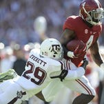 Alabama running back T.J. Yeldon (4) is wrapped up by Texas A&M defensive back Deshazor Everett (29) at Bryant-Denny Stadium in Tuscaloosa, Ala. on Saturday October 18, 2014.