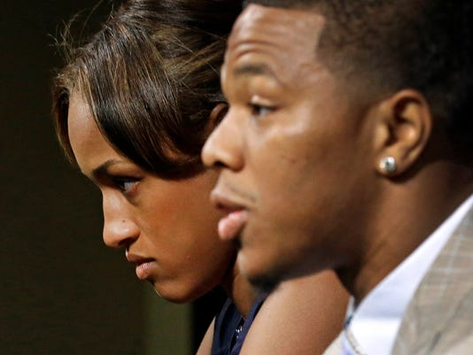 Janay Rice, back left, looks on as her husband, Baltimore Ravens running back Ray Rice, speaks during an NFL football news conference, Friday, May 23, 2014, at the team's practice facility in Owings Mills, Md. Ray Rice spoke to the media for the first time since his arrest for assaulting his fiance, now his wife, at a casino in Atlantic City, N.J.  (AP Photo/Patrick Semansky)