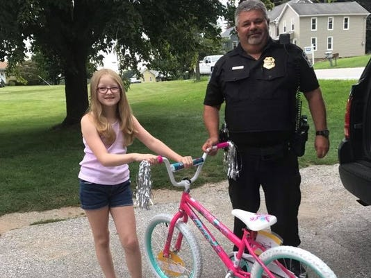 Chief Tim Hippensteel gives Katelyn Thompson a new bicycle