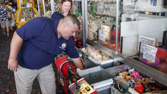 Joseph Cheessere and Christine Donahue, investigators with the statet Division of Consumer Affairs, inspect crane games at Jenkinson's on the Point Pleasant Beach boardwalk.