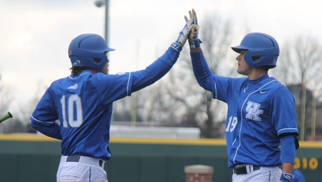 First baseman Evan White (19) congratulates second baseman Luke Becker (10) during a game against Buffalo on March 4, 2016.