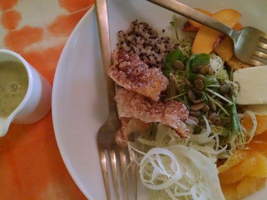 A dish of seasonal fruits, salad and fried pork belly at Chi Chi.
