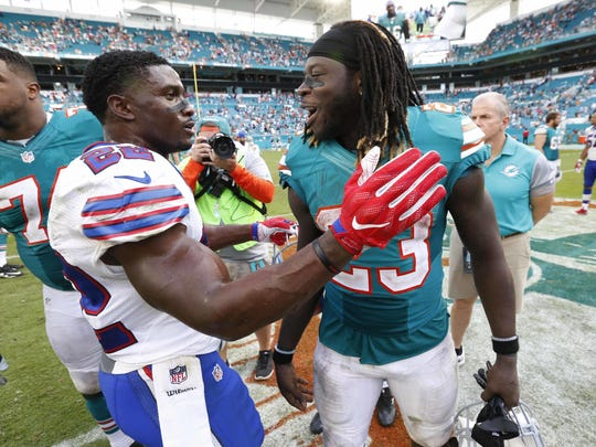 Buffalo Bills running back Reggie Bush (22) congratulates Miami Dolphins running back Jay Ajayi (23) at the end of an NFL football game, Sunday, Oct. 23, 2016, in Miami Gardens, Fla. Ajayi tied an NFL record by surpassing 200 yards rushing for the second game in a row, helping the Miami Dolphins rally past the Buffalo Bills 28-25. (AP Photo/Wilfredo Lee)
