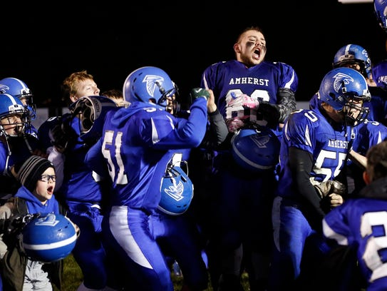 Amherst players celebrate their 49-18 victory against Spencer/Columbus Catholic in the second round of the Division 5 football playoffs Oct. 27.