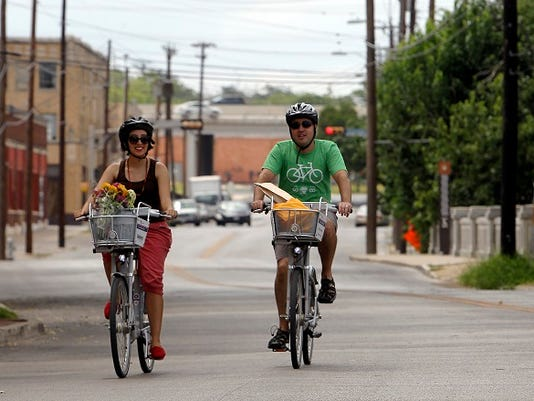 Claudia Zarazua (left) and Ruben Mancha utilize the city's bike-sharing program to run errands around Downtown San Antonio.