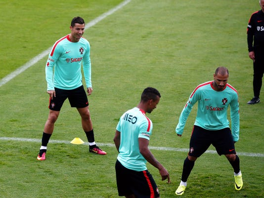 Portugal's Christiano Ronaldo, left, Nani, center, and Ricardo Quaresma, exercise with the ball during a training session in Marcoussis, near Paris, France, Monday, July 4, 2016. Portugal will face Wales in a Euro 2016 semi final soccer match in Lyon on Wednesday, July 6, 2016. (AP Photo/Thibault Camus)