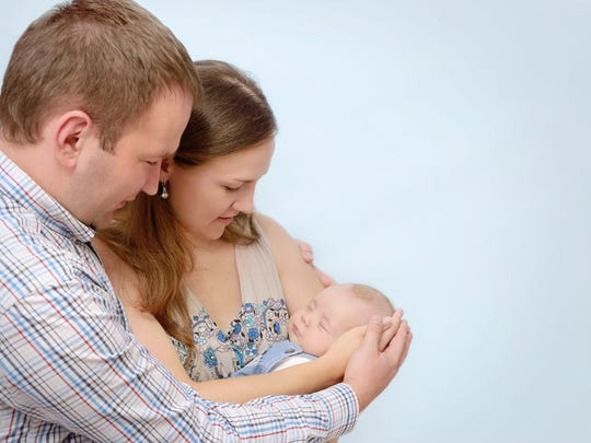 A married couple cradling their newborn baby in their arms.