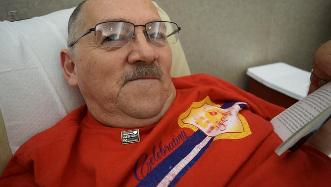 Wendell Clark reads while donating blood. Clark was inducted this year into the Fresenius Kabi National Donation Hall of Fame for his longtime blood donations.