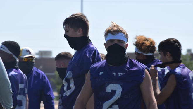 Casey Elam (2) and his River Road teammates wear masks after breaking from practice during two-a-days last week.