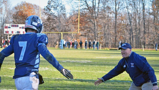 York High School school resource officer and assistant football coach Shaun Darrow, right, congratulates senior captain Riley Linn after a 40-yard interception return for a touchdown in a recent semifinal win. The town's school resource officer program was discussed at the Aug. 10 meeting of the Board of Selectmen.