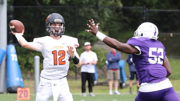 Mamaroneck quarterback Tommy Dillon is pressured by