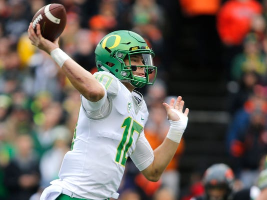 FILE - In this Nov. 26, 2016, file photo, Oregon quarterback Justin Herbert throws in the first half of an NCAA college football game against Oregon State in Corvallis, Ore. (AP Photo/Timothy J. Gonzalez, File)