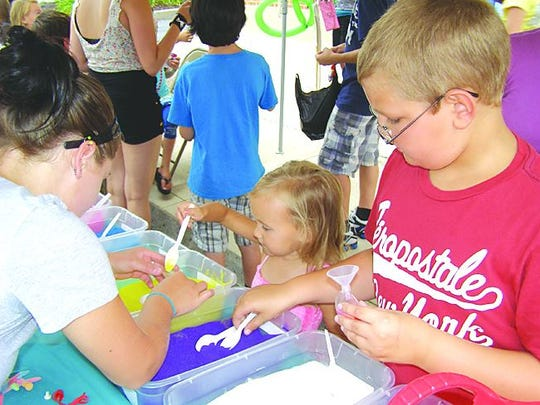 Kids try their hands at sand art at a past Sidewalk Days in Greencastle.
