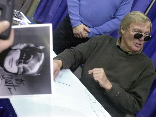 In February 2002, a fan holds a signed photograph of